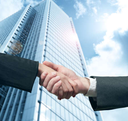 Business handshake with modern office skyscraperの写真素材
