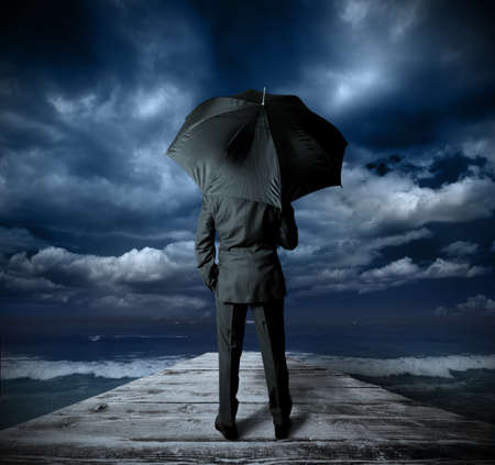 Businessman with umbrella against the storm