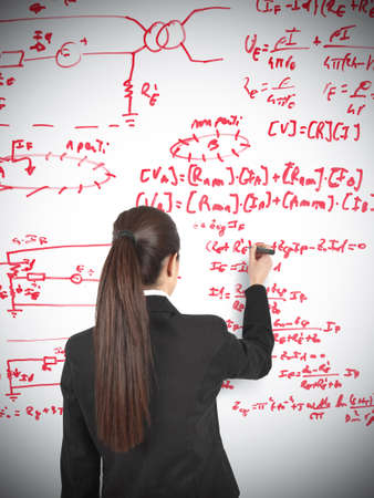 Businesswoman drawing formula in a whiteboard