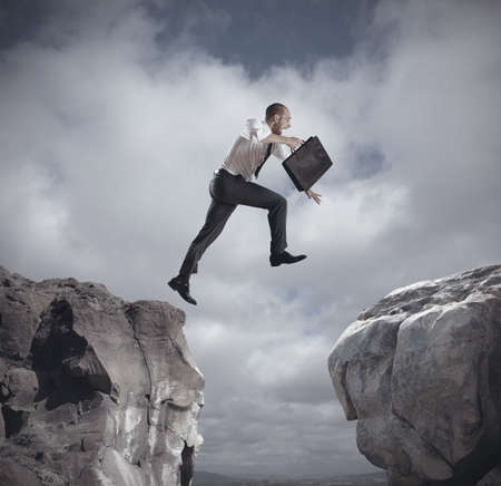 Businessman jumping over the mountains  concept of ambition in business