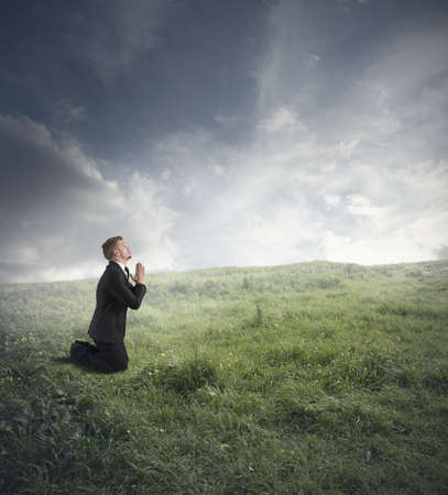 Businessman is praying to solve the financial crisis