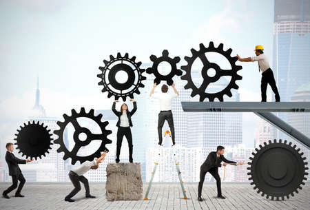 Foto de Teamwork works together to build a gear system - Imagen libre de derechos