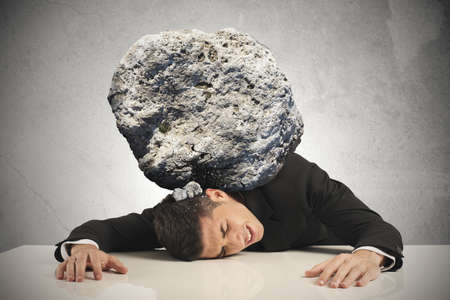 Stress of a businessman with a big rock