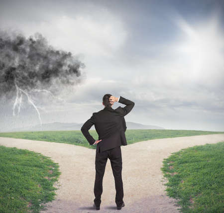 Foto de Businessman at a crossroads with storm and sunshine - Imagen libre de derechos