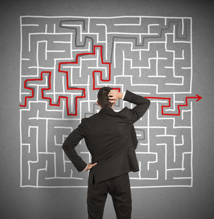 Confused business man seeks a solution to the big labyrinth
