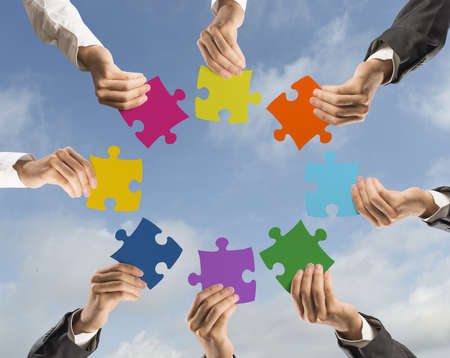Concept of teamwork and integration with businessman holding colorful puzzle