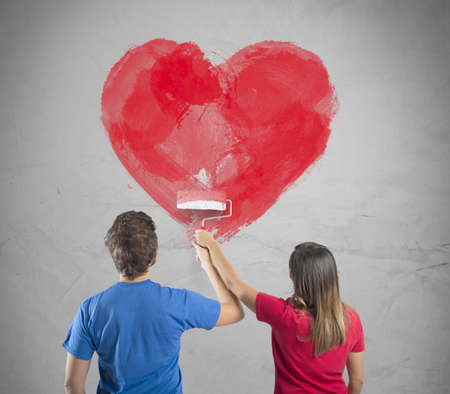Photo pour Young couple drawing a big heart in a wall - image libre de droit