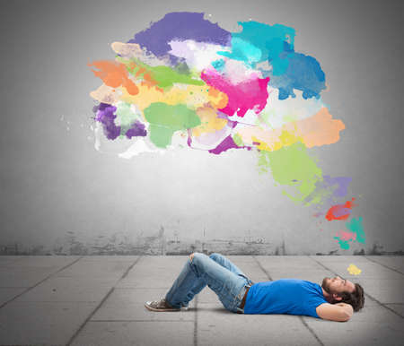 Lying boy think creative with colorful splash