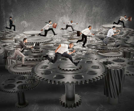 Business people running over a mechanism system