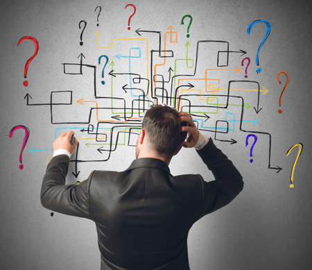 Foto de Businessman trying to solve a maze questions - Imagen libre de derechos