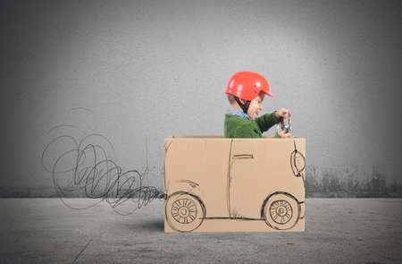 Creative baby plays with his cardboard car