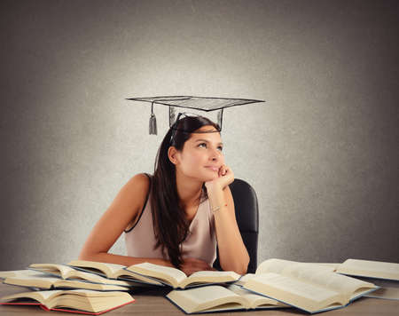 Photo pour Young student between books dreams the graduation - image libre de droit
