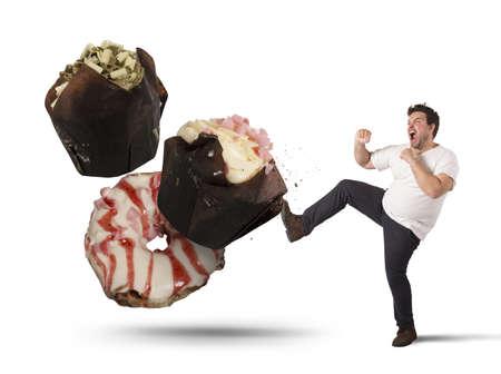 Fat man kicks a high calorie sweet