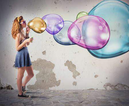 Photo pour Girl has fun making colorful soap bubbles - image libre de droit