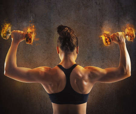 Gym woman train back with fiery dumbbells