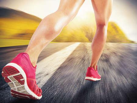 Legs of sporty woman running on asphalt