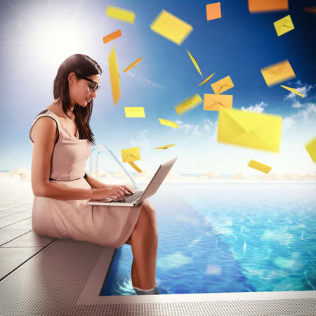 Businesswoman exchange mails with laptop in pool
