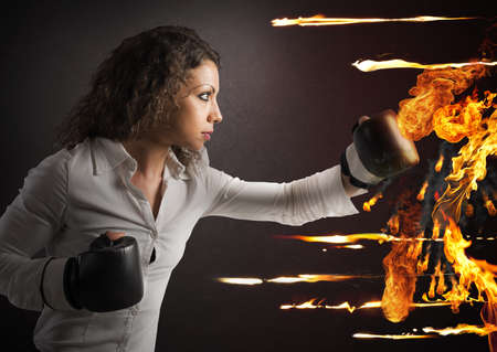 Determined woman with boxing gloves fights fire
