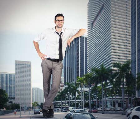 Giant successful businessman leaning against a skyscraper