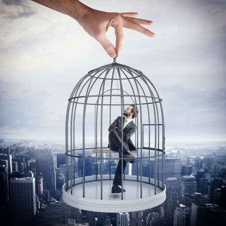 Photo for Businessman sitting in a cage of birds - Royalty Free Image