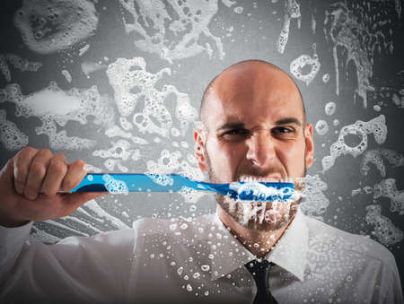 Photo pour Man brushing teeth with a big toothbrush - image libre de droit