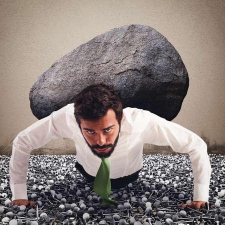 Foto de Businessman holds on back a big boulder - Imagen libre de derechos