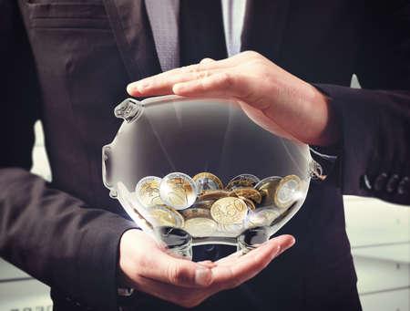 Man holds a transparent piggybank with coins