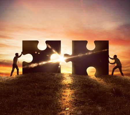 Foto de Men push two puzzle pieces at sunset - Imagen libre de derechos