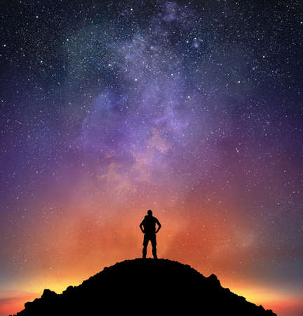 Excursionist on a mountain observe a bright sky full of stars