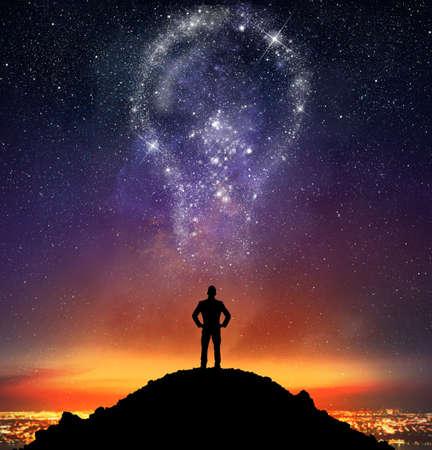 Businessman illuminated by a bright big idea on sky