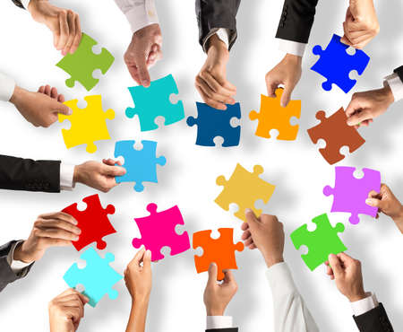 Foto de Business people join the colorful puzzle pieces. Concept of teamwork and integration - Imagen libre de derechos