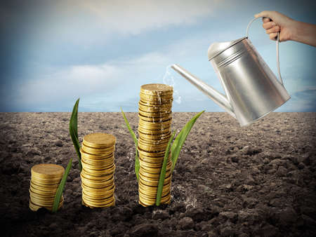 Businessman watering money coins as if they were plants