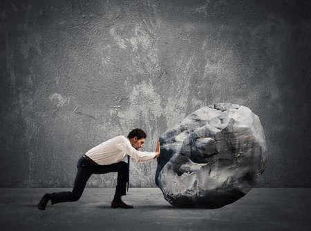 Foto de Businessman pushing a heavy boulder with great effort - Imagen libre de derechos