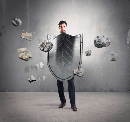 Businessman with shields. concept of protection and defense in the business world