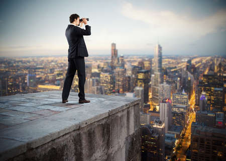 Photo pour Businessman looks at the city from the roof with binoculars - image libre de droit