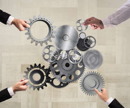 Teamwork of businesspeople work together and combine pieces of gears to a mechanical system