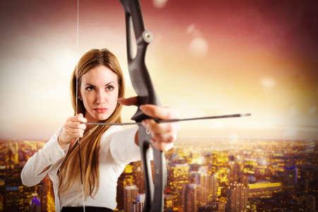 Photo pour Businesswoman with bow and arrow with cityscape view - image libre de droit