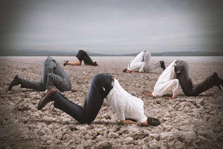 Photo pour Afraid business people hide their head under the ground like an ostrich. Fear of crisis concept - image libre de droit