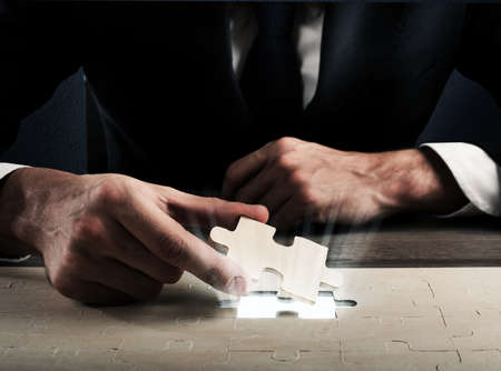 Photo for Businessman complete a puzzle inserting last piece - Royalty Free Image