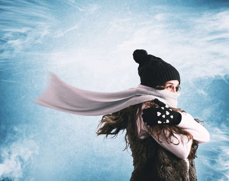 Photo pour Woman with woolen scarf and hat trying to shelter from the winter cold - image libre de droit