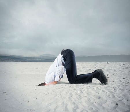 Foto de Afraid businessman hide his head under the ground like an ostrich. Fear of crisis concept - Imagen libre de derechos