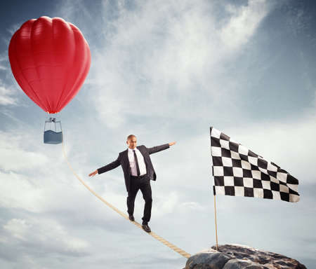 Photo pour Business concept of businessman who overcome the problems reaching the flag on a rope - image libre de droit