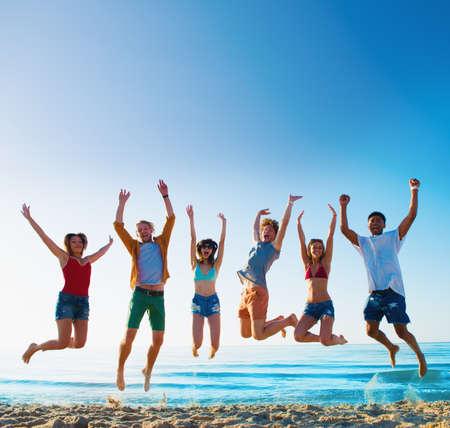 Photo pour Happy smiling friends jumping at the beach - image libre de droit