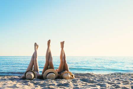 Foto de Group of happy friends having fun at ocean beach at dawn with legs up - Imagen libre de derechos