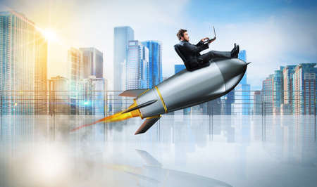 Photo pour Fast internet concept with a businessman with laptop over a rocket - image libre de droit