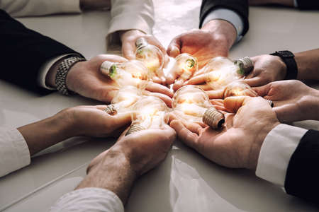 Photo pour Teamwork and brainstorming concept with businessmen that share an idea with a lamp. Concept of startup - image libre de droit