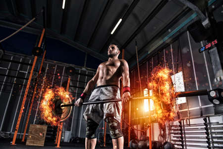 Photo for Athletic man works out at the gym with a fiery barbell - Royalty Free Image