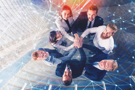 Foto de Business people putting their hands together with internet network effects. Concept of integration, teamwork and partnership. double exposure - Imagen libre de derechos