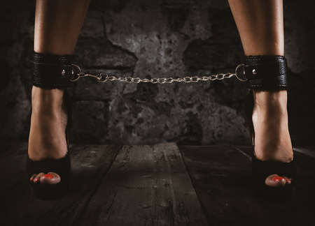 Sensual provocation of a sexy bdsm woman with chained legs