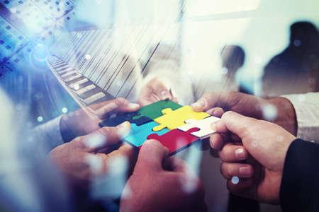 Foto de Business people join puzzle pieces in office. Concept of teamwork and partnership. double exposure with light effects - Imagen libre de derechos